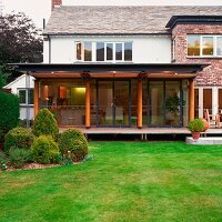 Elegant house with lawn and shrubs in garden