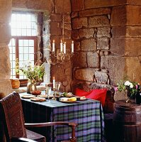 Table set with dinner on tartan tablecloth below lit candles in chandelier in corner of rustic room with stone walls