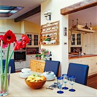 Open-plan, country-house-style, cream, wooden kitchen with blue upholstered chairs