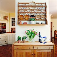 Simple, half-height wooden cabinet below plate rack on narrow partition