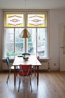 Retro chairs around kitchen table in front of window with stained glass upper panes in simple dining room