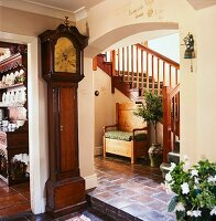 Antique longcase clock next to wide, arched doorway with view of rustic bench against wooden staircase in foyer