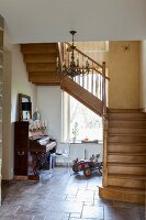 Wooden staircase in tiled hallway with antique piano and vintage-style toy car