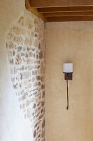 Wrought iron sconce lamp with white lampshade next to stone wall