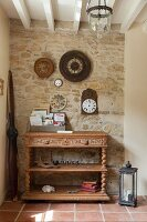 Console table with turned legs, shelves and carved drawer fronts below collection of vintage-style clocks on stone wall