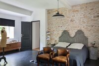 Vintage chairs at foot of double bed with curved, wooden headboard against stone wall