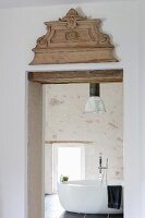 Carved ornament above lintel of interior door with view of free-standing bathtub in country-house ambiance