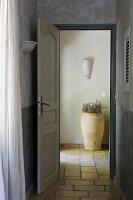 Open door leading into foyer with tiled floor and terracotta pot