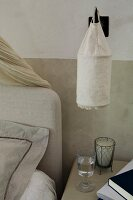 Wall-mounted lamp with linen sacking lampshade above bedside table next to bed with headboard against painted dado