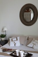Breakfast tray on bed with arranged scatter cushions below round mirror with rustic wooden frame