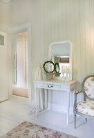 Small dressing table and antique chair with floral upholstery in white-panelled bedroom