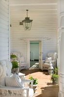 White wicker chairs and geraniums in sunny loggia with white wooden panelling