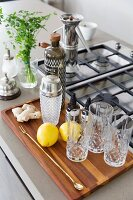 Wooden tray of glasses and cocktail equipment next to gas hob on wooden counter
