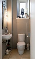 White toilet against grey panelled wall below window; sink below framed mirror with modern strip light