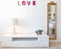 Postmodern table lamp on low white sideboard below pink decorative letters spelling 'LOVE' next to gilt-framed mirror