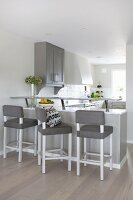 Bar stools with grey seats at counter in open-plan minimalist kitchen