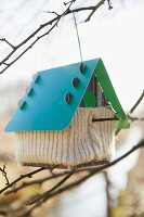 A birds house with a knitted cover hanging on a twig