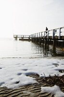 A snow-covered lakeside with people on a wooden jetty in the background