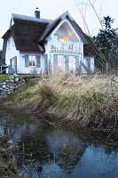 A small stream at the bottom of a garden with a thatched roof house in the background