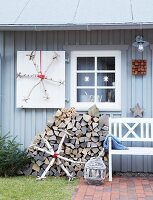 Homemade snowflakes made from birch wooden in front of a grey-painted wooden house