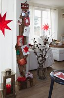 A living room decorated for Christmas – postcards hung on a piece of driftwood nailed to the wall with Christmas decorations and presents