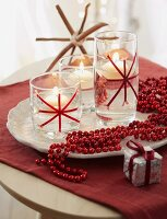 Christmas decoration – a string of red beads next to floating candles on a white dish