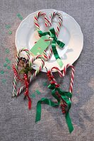 Candy canes arranged in love-hearts decorated with ribbon and sprigs of berries as festive table decorations