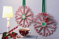 Candy-cane love-hearts arranged in festive wreaths tied with ribbons on wall