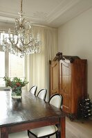 Rustic wooden table and neo-antique, upholstered chairs below crystal chandelier in grand dining room