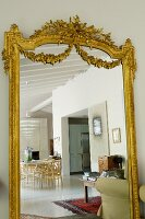 Antique mirror with ornate, gilt frame reflecting dining area
