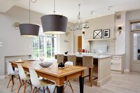 Classic chairs with white shell seats at wooden table below pendant lamps with grey lampshades in front of island counter and bar stools in open-plan, country-house kitchen