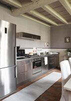 Contemporary, stainless steel kitchen counter in rustic kitchen with wood-beamed ceiling