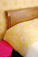 Detail of bed with wooden headboard, floral bed linen and floral wallpaper