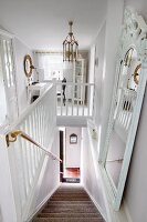 Dramatic view down staircase with white wooden balustrade