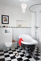 Free-standing, vintage bathtub on chequered floor against wall with white tiled dado and floor-level shower to one side