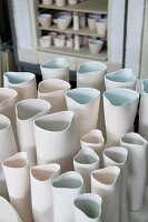White, hand-crafted ceramic vases of various sizes in workshop