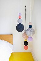 Strings of knitted balls hung next to bed above yellow wooden floor