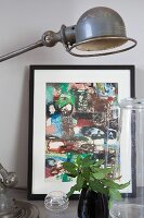 Still-life arrangement of black-framed picture, retro table lamps an glass vessels