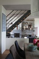 View from dining area into elegant, open-plan interior with steel staircase and wall-mounted shelves