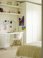Desk and classic chair next to white wardrobe in teenager's bedroom