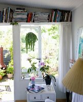 Storage solution: bookshelf above French windows with view into garden