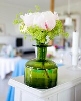 Peony in green vintage bottle on white wooden surface
