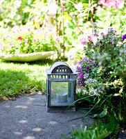 Tealight in lantern on stone flag in flowering garden