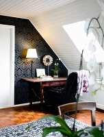 Desk against black wallpaper below sloping, white, wood-clad ceiling