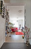 View into comfortable, open-plan living area with bookcase, retro standard lamp and flowering branches in doorway in renovated town-house apartment