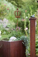 Planter with ornamental crown and pillar made from rusty metal