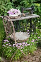Vintage chair in front of bowl of flowers and wicker wreath on old sewing machine in flowering garden