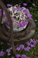 Arrangement of purple flowers in bowl in wicker wreath on chair in garden
