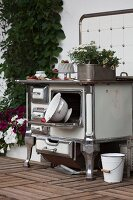 Vintage cooker and kitchen utensils decorating wooden terrace