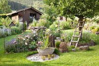 Rustic garden with flowering beds, aquatic plants in large bowl set in gravel and shed in background